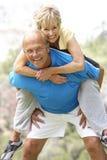 Couples aînés s'exerçant en stationnement Images libres de droits