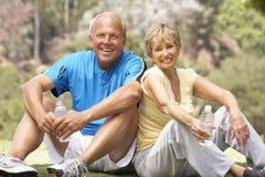 Couples aînés s'exerçant en stationnement Image libre de droits