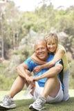 Couples aînés s'exerçant en stationnement Images stock