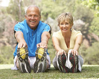 Couples aînés s'exerçant en stationnement Photo stock