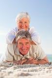 Couples aînés se couchant sur la plage Image stock