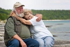 Couples aînés se reposant au bord de rivages Image libre de droits