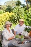 Couples aînés se reposant dans leur jardin Image libre de droits