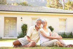 Couples aînés se reposant en dehors de la maison rêveuse Images stock