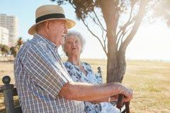 Couples aînés se reposant en stationnement Image libre de droits