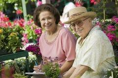 Couples aînés se reposant parmi des fleurs Photos stock