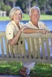 Couples aînés se reposant sur le banc de stationnement par Lake Photographie stock libre de droits
