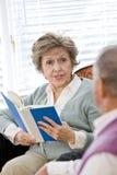 Couples aînés se reposant sur le relevé de divan de salle de séjour Photos libres de droits