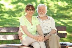 Couples aînés se reposant sur un banc de stationnement Photo libre de droits