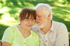 Couples aînés se reposant sur un banc de stationnement Images stock