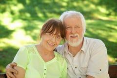 Couples aînés se reposant sur un banc de stationnement Photographie stock