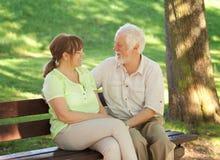 Couples aînés se reposant sur un banc de stationnement Photos stock