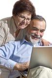Couples aînés sur l'ordinateur portatif Photographie stock libre de droits