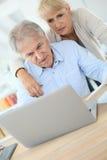 Couples aînés sur l'ordinateur portatif Photographie stock