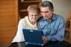 Couples aînés sur l'ordinateur portatif Images stock