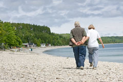 Couples aînés sur la plage rocheuse Photos libres de droits