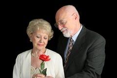 Couples aînés sur le noir - geste romantique Photo stock