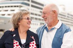 Couples aînés sur le rivage devant le bateau de croisière Photo libre de droits