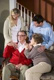 Couples aînés sur le sofa à la maison avec les enfants adultes Photo stock