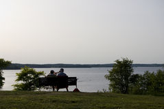 Couples aînés sur un banc de stationnement sur égaliser d'étés. Images libres de droits