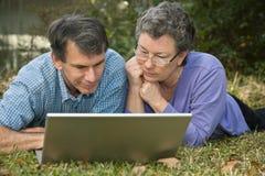 Couples aînés surfant le Web Photographie stock libre de droits
