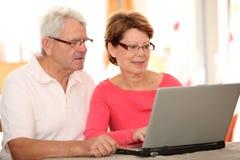 Couples aînés utilisant l'Internet Photos libres de droits