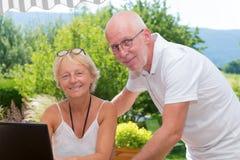 Couples aînés utilisant l'ordinateur portable à la maison Photo libre de droits