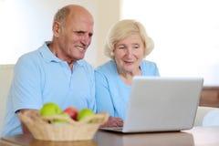 Couples aînés utilisant l'ordinateur portatif à la maison Image libre de droits