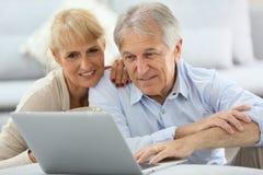 Couples aînés utilisant l'ordinateur portatif à la maison Photo stock
