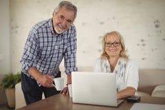 Couples aînés utilisant l'ordinateur portatif à la maison Photos libres de droits
