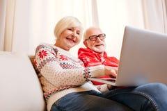 Couples aînés utilisant l'ordinateur portatif Photographie stock libre de droits