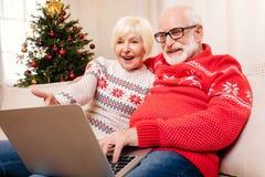 Couples aînés utilisant l'ordinateur portatif Photos stock