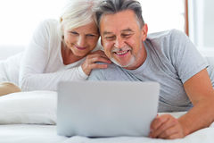 Couples aînés utilisant l'ordinateur portatif Photographie stock