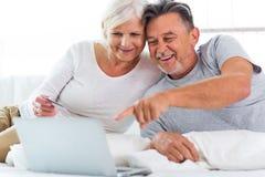 Couples aînés utilisant l'ordinateur portatif Images stock