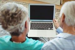 Couples aînés utilisant l'ordinateur portatif Image stock