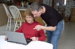 Couples aînés utilisant l'ordinateur portatif, Internet, technologie Photographie stock libre de droits