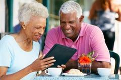 Couples aînés utilisant la tablette au café extérieur Images stock