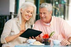 Couples aînés utilisant le café d'ordinateur de tablette