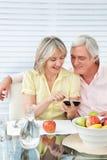 Couples aînés utilisant le smartphone Photos stock