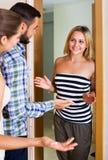 Couples accueillant l'ami à la porte Photographie stock libre de droits