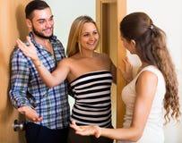 Couples accueillant l'ami à la porte Images libres de droits