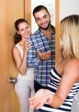 Couples accueillant l'ami à la porte Photos libres de droits