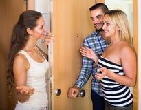 Couples accueillant l'ami à la porte Photos stock
