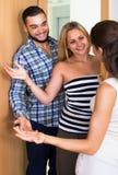 Couples accueillant l'ami à la porte Images stock