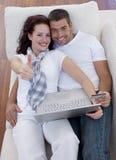 Couples achetant en ligne à la maison avec des thums vers le haut Image stock