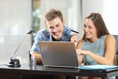 Couples achetant en ligne ensemble à la maison Images stock