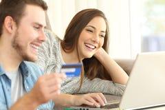 Couples achetant en ligne sur un divan Photo libre de droits