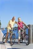 Couples actifs aînés heureux sur des bicyclettes Photographie stock libre de droits