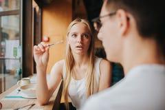 Couples adolescents étonnés tenant le problème positif de relations de conflit d'essai de grossesse d'homme d'exposition de femme Image libre de droits