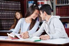 Couples adolescents affectueux tenant des mains au Tableau dedans Photographie stock